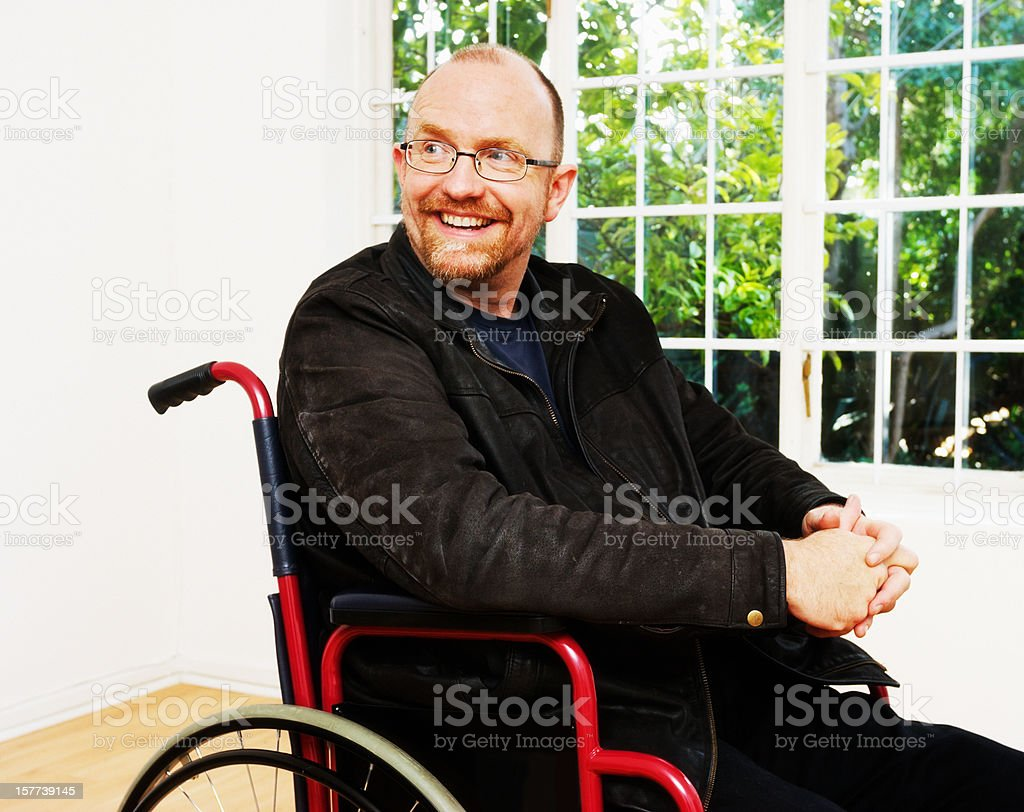 Cheerful-looking mature man sitting in wheelchair smiles over shoulder stock photo