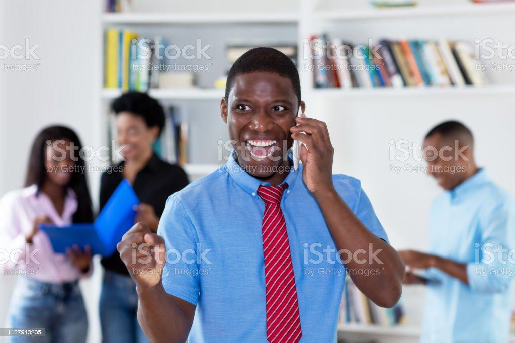 Empresario afroamericano que anima con el lazo en el teléfono con sus colegas - foto de stock