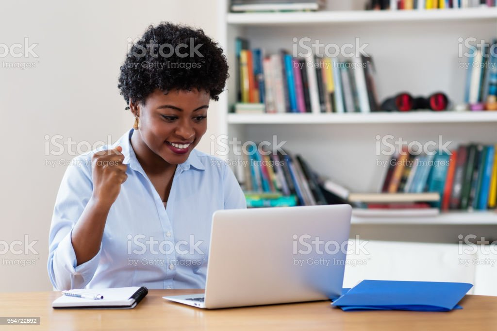 Cheering african american businesswoman at computer stock photo