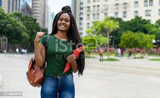 Cheering african american female student with braid and copy space outdoor in summer in city
