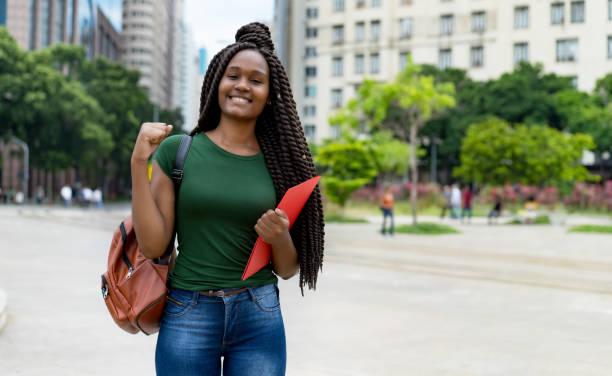 Animando a una estudiante afroamericana con trenza y espacio de copia - foto de stock