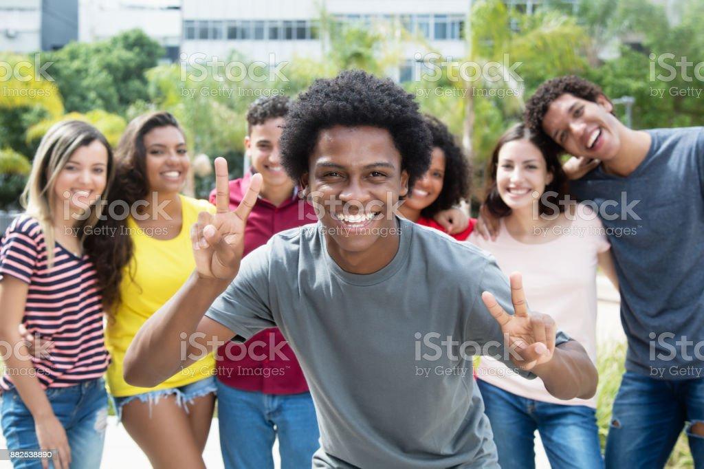 Torcendo o cara americana Africano com grupo de amigos internacionais - foto de acervo