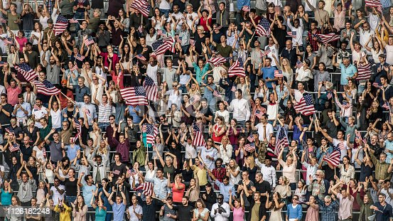 Large crowd of American sports fans on a stadium cheering and waving US flags.