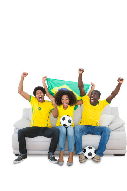 Cheering brazilian football fans in yellow on the sofa stock photo
