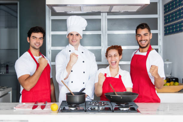 cheering chef with team at kitchen - cooker happy imagens e fotografias de stock