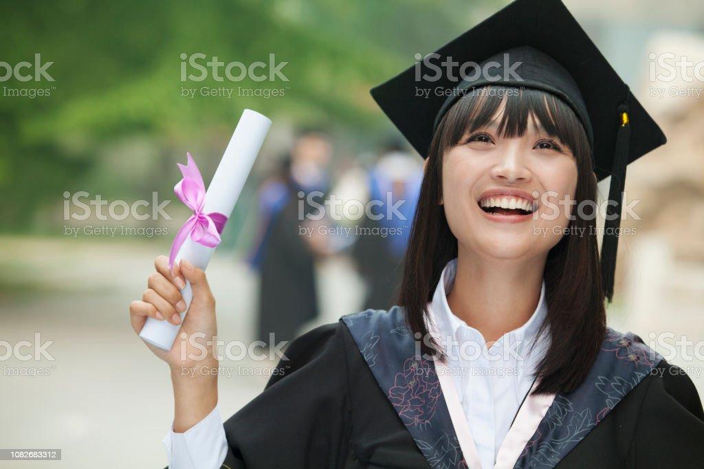 Jubelnde chinesischen Studenten im Abschluss Mütze und Mantel mit Diplom – Foto