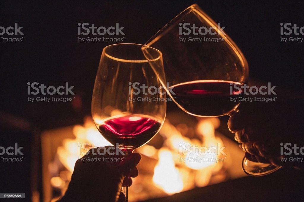 Couple de vivats, tenant chacun un verre de vin devant un feu de camp. - Photo