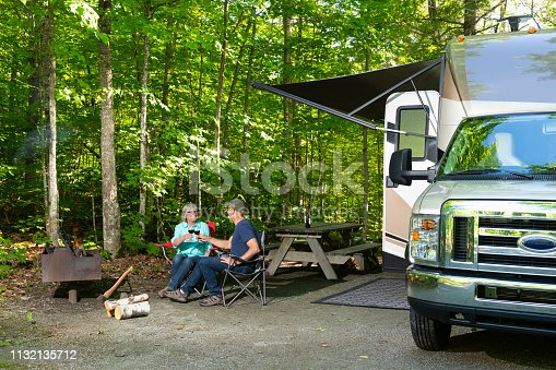Couple relaxing in camping. Man and woman drinking red wine.