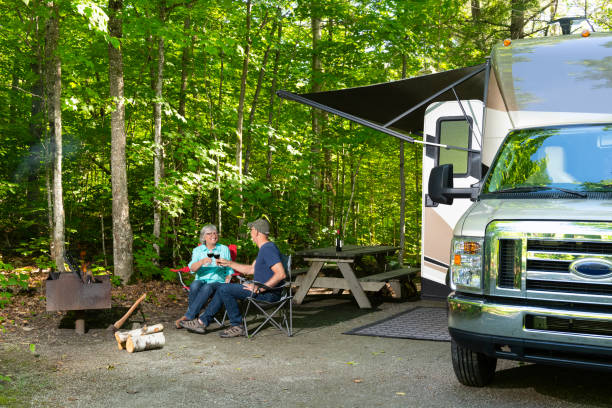 Cheering couple near campfire Couple relaxing in camping. Man and woman drinking red wine. motor home stock pictures, royalty-free photos & images