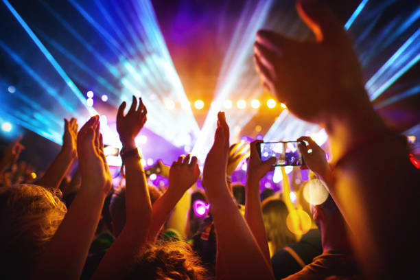Cheering crowd at a concert. Rear view of excited crowd enjoying a DJ performance at a festival. There are many raised hands, some of the holding cell phones and taping the show. People in foreground are released. nightclub stock pictures, royalty-free photos & images