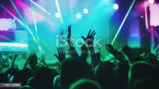 Rear view of excited crowd enjoying a concert performance of a unrecognizable artist. Raised hands of fans are in the focus against green and purple lit stage.