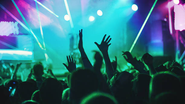 Cheering crowd at a concert. Rear view of excited crowd enjoying a concert performance of a unrecognizable artist. Raised hands of fans are in the focus against green and purple lit stage. nightclub stock pictures, royalty-free photos & images