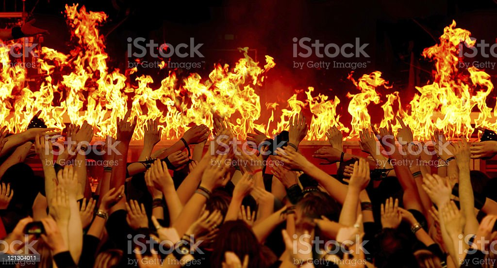 cheering crowd in front of fire on stage royalty-free stock photo