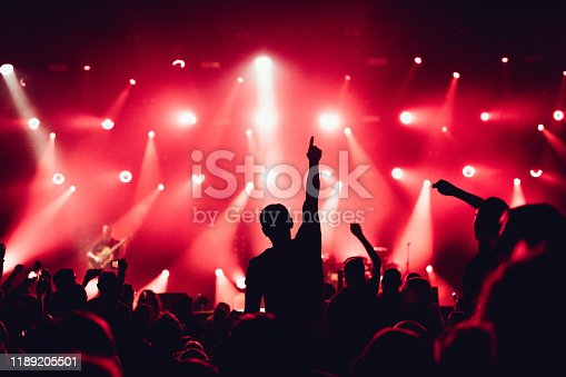 Colorful crowd of uncrecognized people of a big music festival or concert in a stage lights as a beautiful background
