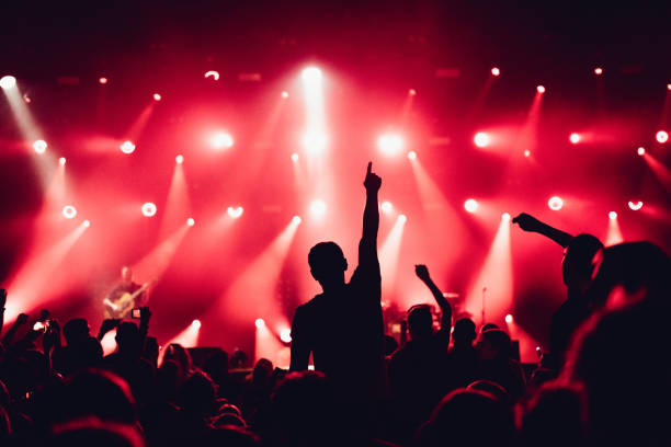cheering crowd of unrecognized people at a rock music concert. concert crowd in front of bright stage lights. concert audience at music concert. smoke, concert spotlights. - music style stock pictures, royalty-free photos & images