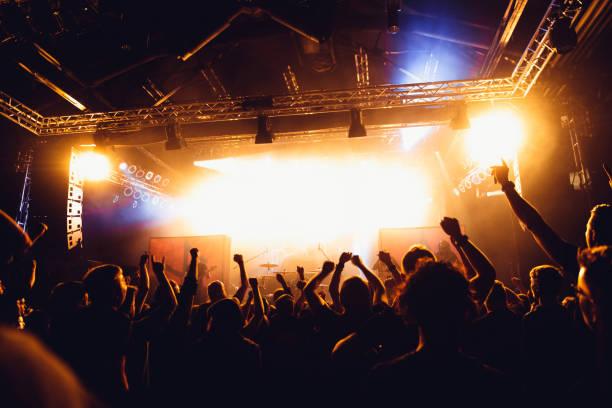 在搖滾音樂會上,歡呼的人群不被認出來。音樂會人群在明亮的舞臺燈光和煙霧面前。音樂會的觀眾在音樂會上。 - music 個照片及圖片檔