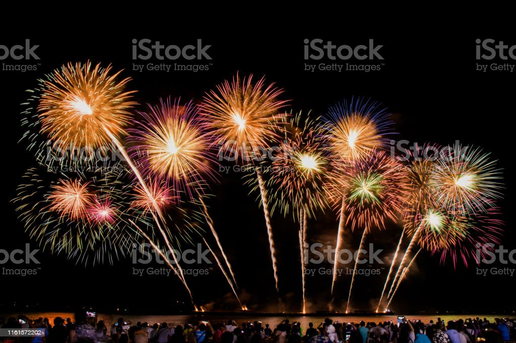 cheering crowd watching colorful fireworks and celebrating on the beach during festival cheering crowd watching colorful fireworks and celebrating on the beach during festival Anniversary Stock Photo