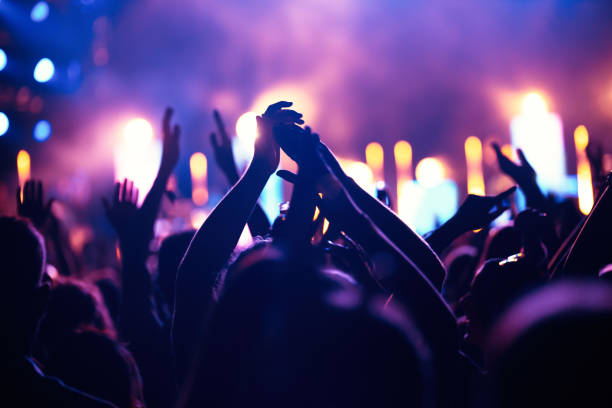 Cheering crowd with hands in air at music festival Happy cheering crowd with hands in air at music festival nightclub stock pictures, royalty-free photos & images