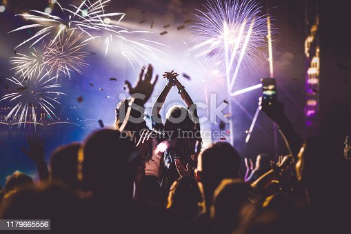 istock cheering crowd with raised hands and falling confetti at concert - music festival 1179665556