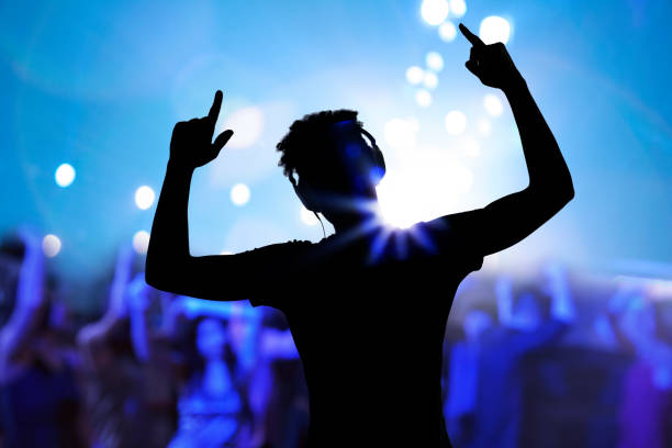 Cheering disco DJ performing with arm raised at concert music festival stock photo