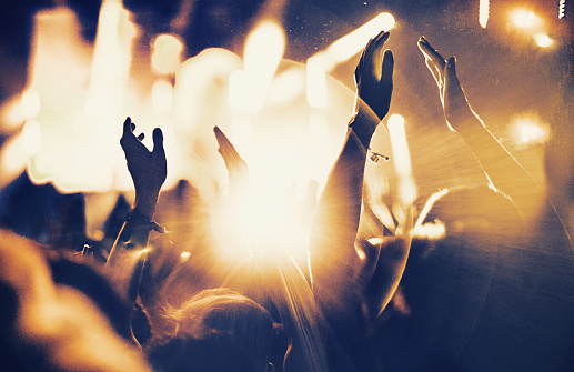 Rear view of large group of unrecognizable people at concert. Their hands are in the air, clapping. Beige stage lights in the background. Two people in foreground are released.