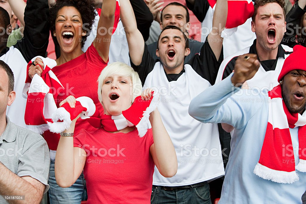 Cheering fans at football match stock photo