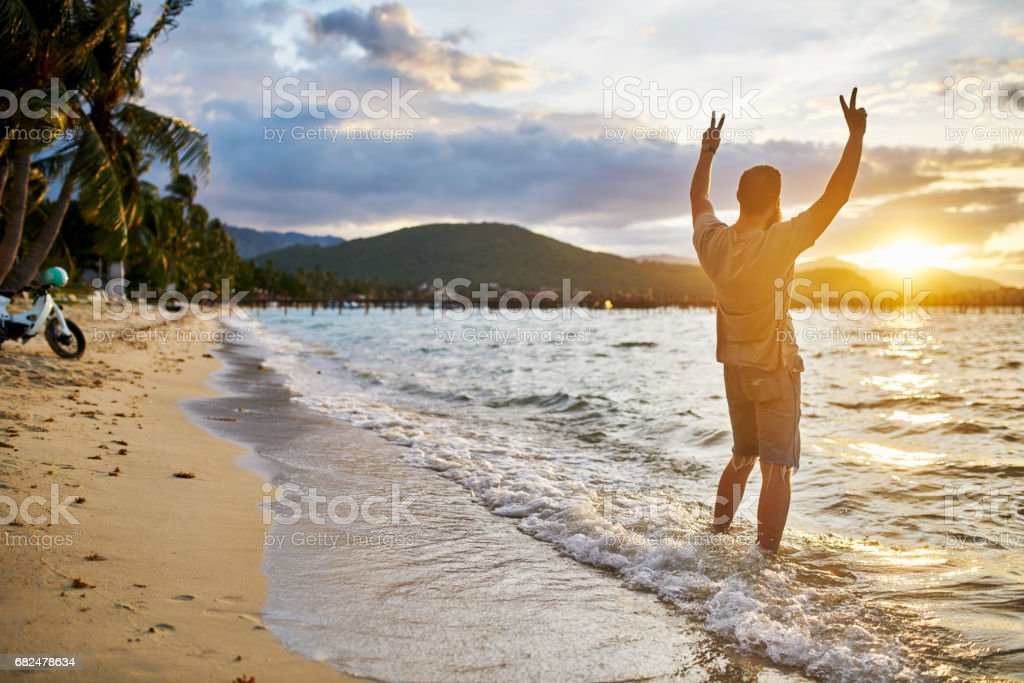cheering farang man passionately observing sunset by himself in thailand royalty-free stock photo