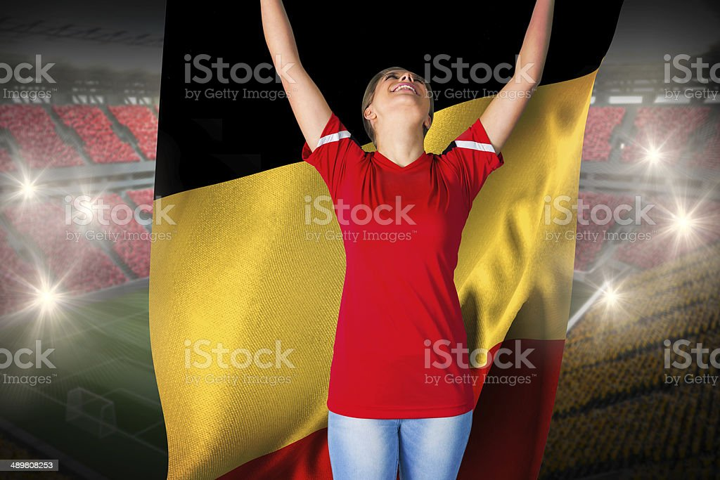 Cheering football fan in red holding belgium flag foto
