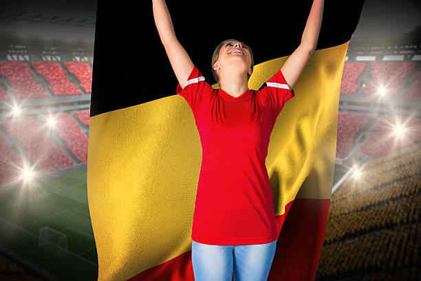 Cheering football fan in red holding belgium flag stock photo