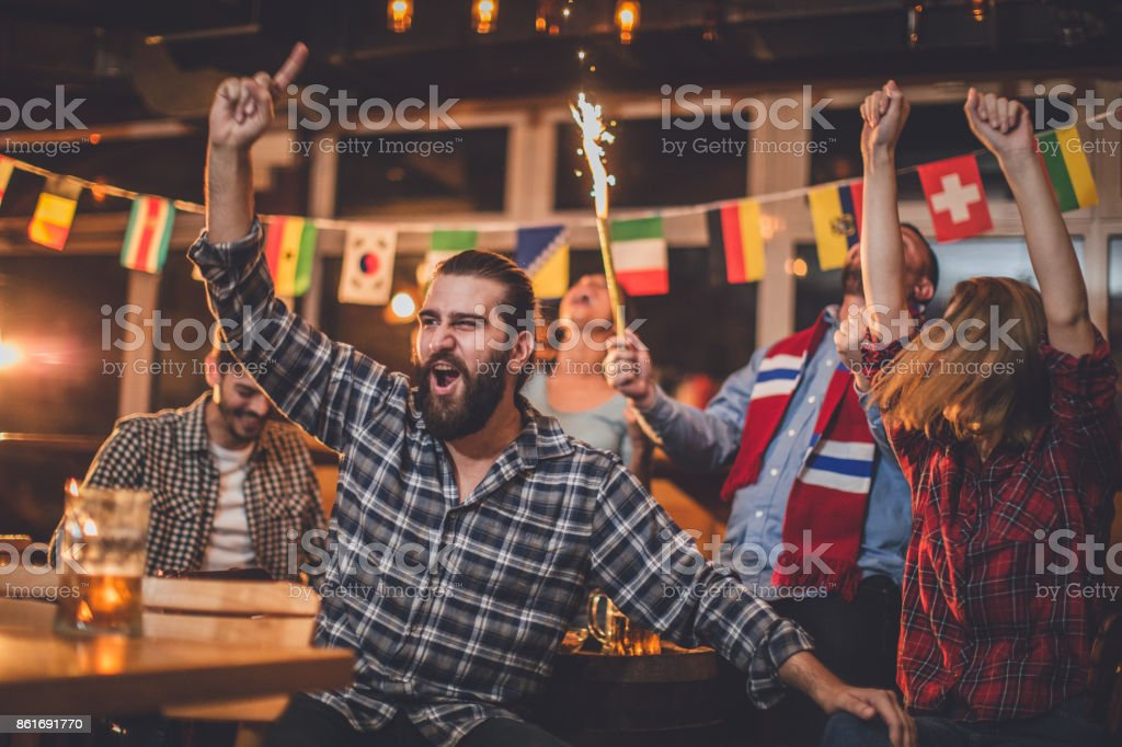 Group of close friends watching a game at the bar and cheering for...