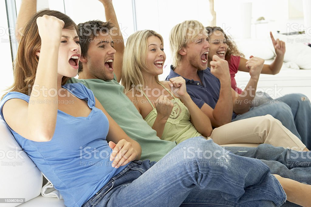 Cheering friends watching game on TV royalty-free stock photo