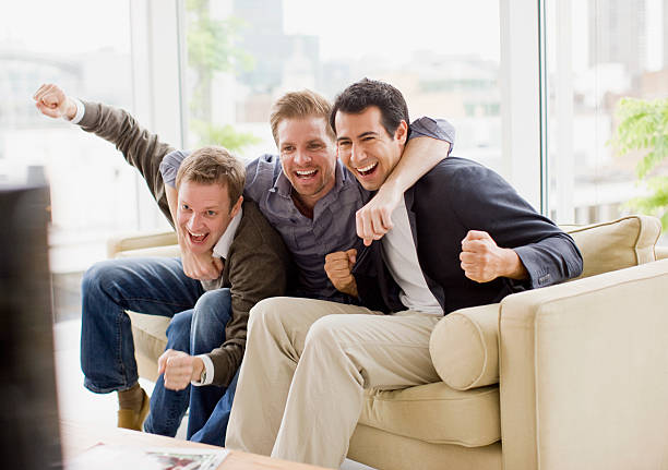 Cheering friends watching television stock photo