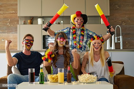 four very happy fans watching football match at home cheering for germany
