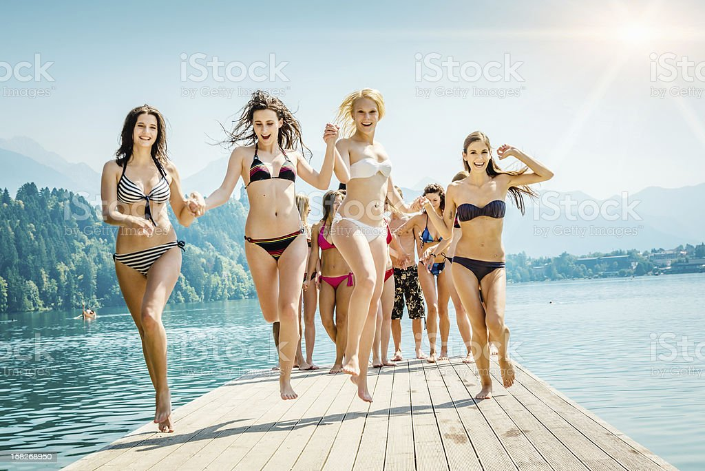 Cheering Girls at the Lake Summer Vacation Group of cheering young adults, girls in bikinis in the front row, running and jumping over a jetty at a lake on a beautiful sunny summer day. Adult Stock Photo