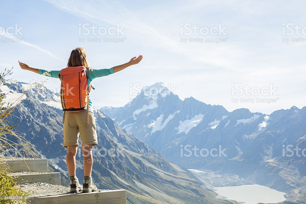 Hiker stands on a mountain top arms outstretched for freedom and...