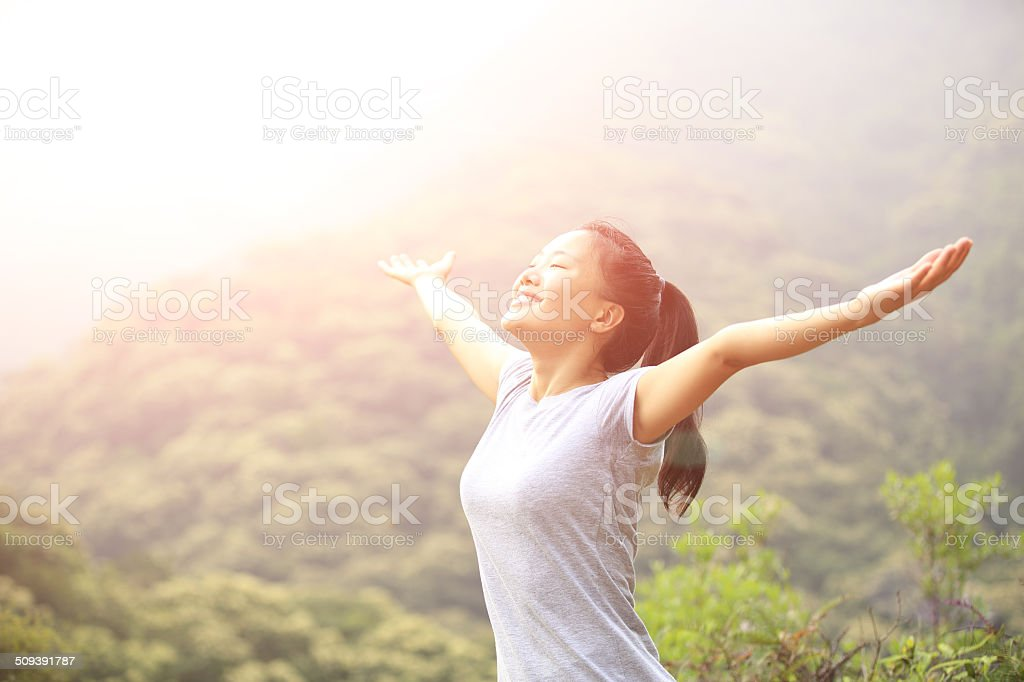 cheering hiking woman open arms at mountain peak stock photo