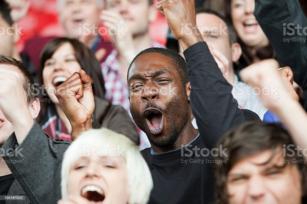 Cheering man at football match stock photo