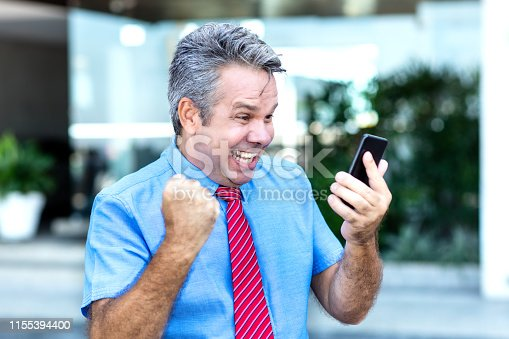 istock Cheering mature businessman receiving message with good news 1155394400
