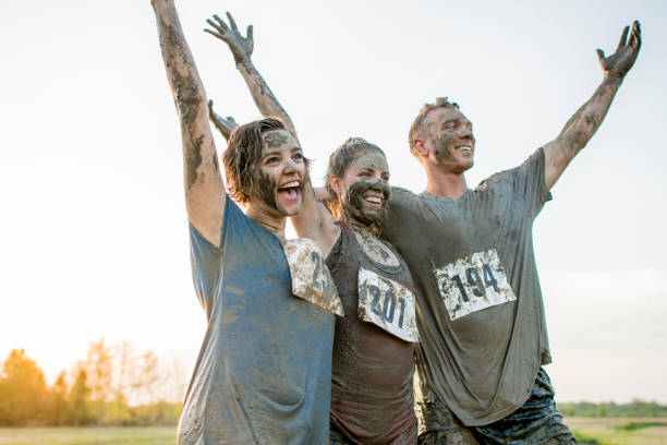 Cheering Two Caucasian women and a Caucasian man are outdoors, participating in a mud run. They are wearing athletic clothing and shoes. They are covered in mud. They are standing and cheering with their arms in the air. mud run stock pictures, royalty-free photos & images