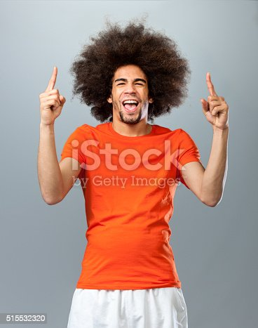 three quarter length shot of a screaming and shouting man, making number one sign with big afro hair in orange T-shirt fan of the Dutch soccer team, looking at the camera on gray background