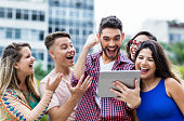istock Cheering spanish hipster student with tablet computer and group of cheering international students 1130074359