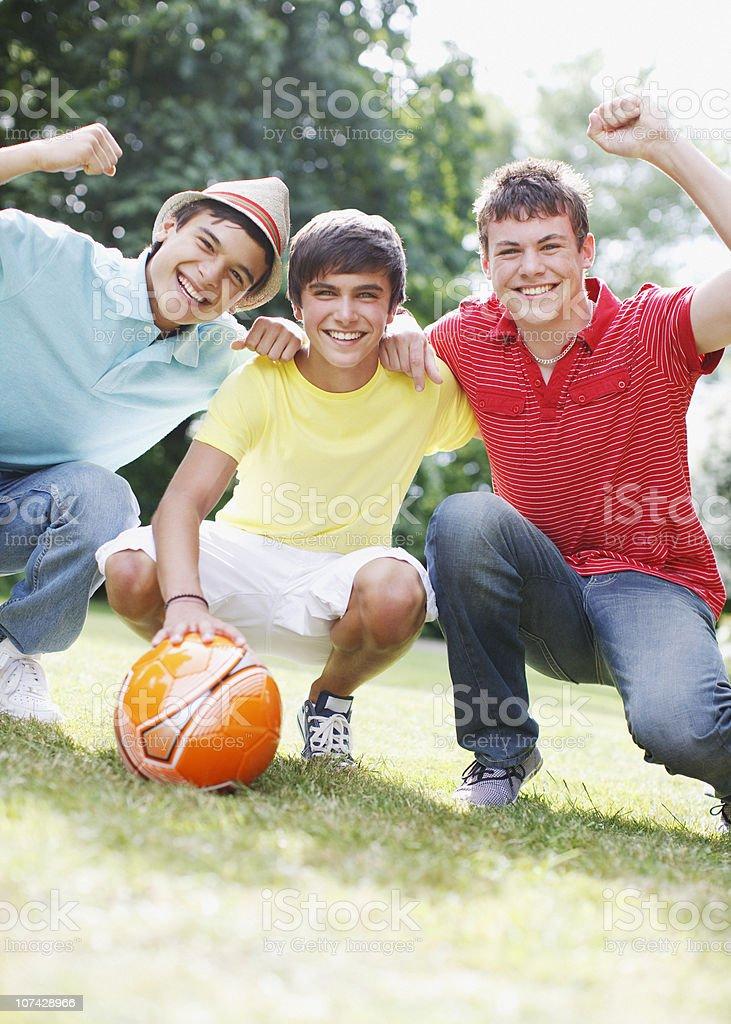 Cheering teenage boys with soccer ball royalty-free stock photo