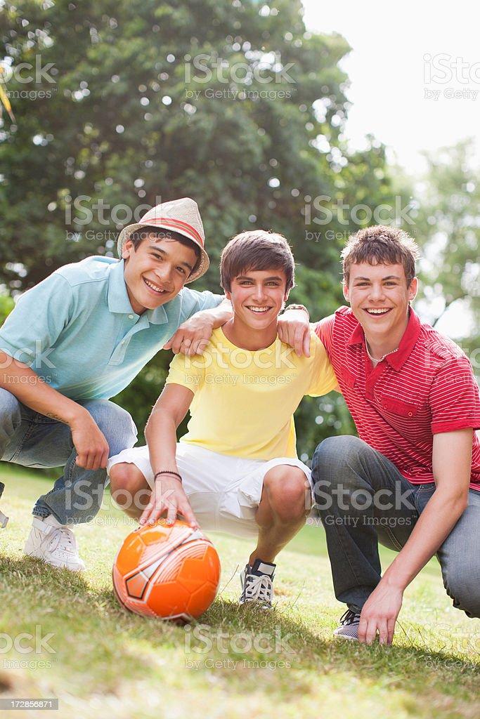 Cheering teenage boys with soccer ball stock photo