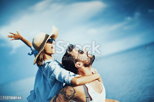 Young couple having fun at the beach. Man is carrying his girlfriend on his back. They are laughing and enjoying summer afternoon.