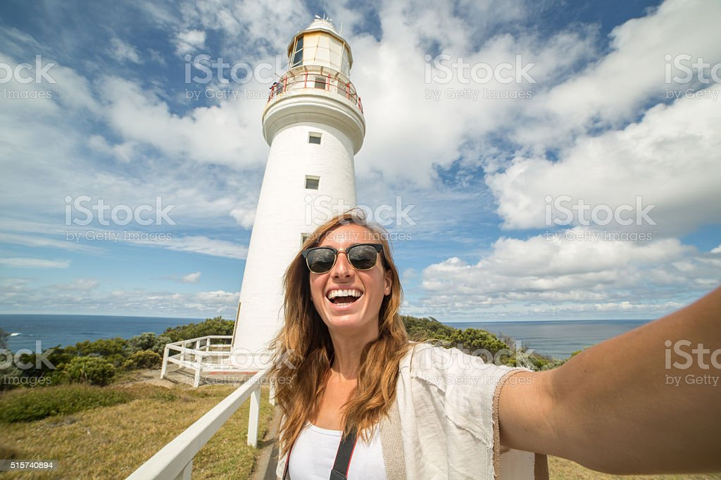 Cheering tourist woman takes selfie portrait with Cape Otway lighthouse stock photo