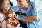 A young nurse laughing with a little girl in her wheelchair at the hospital