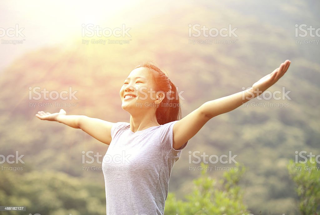 cheering woman open arms at mountain peak stock photo