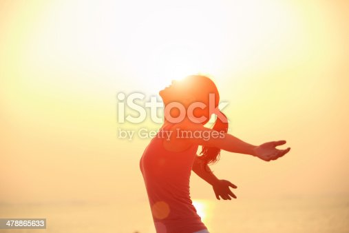 istock cheering woman open arms  at sunrise beach 478865633