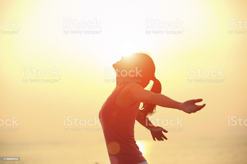 cheering woman open arms  at sunrise beach stock photo
