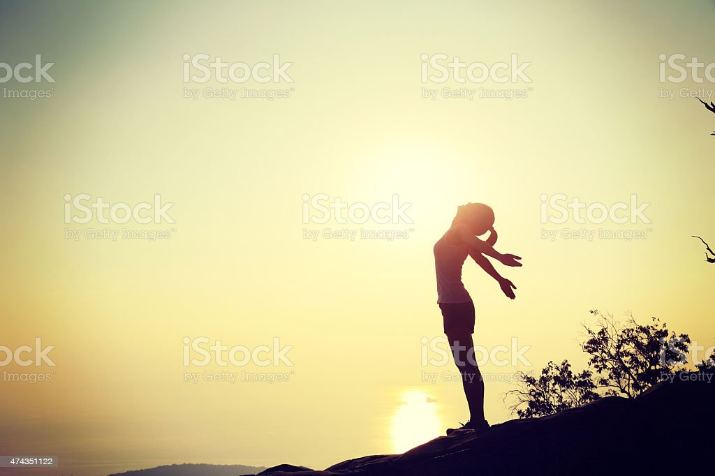 cheering woman open arms at sunset mountain peak
